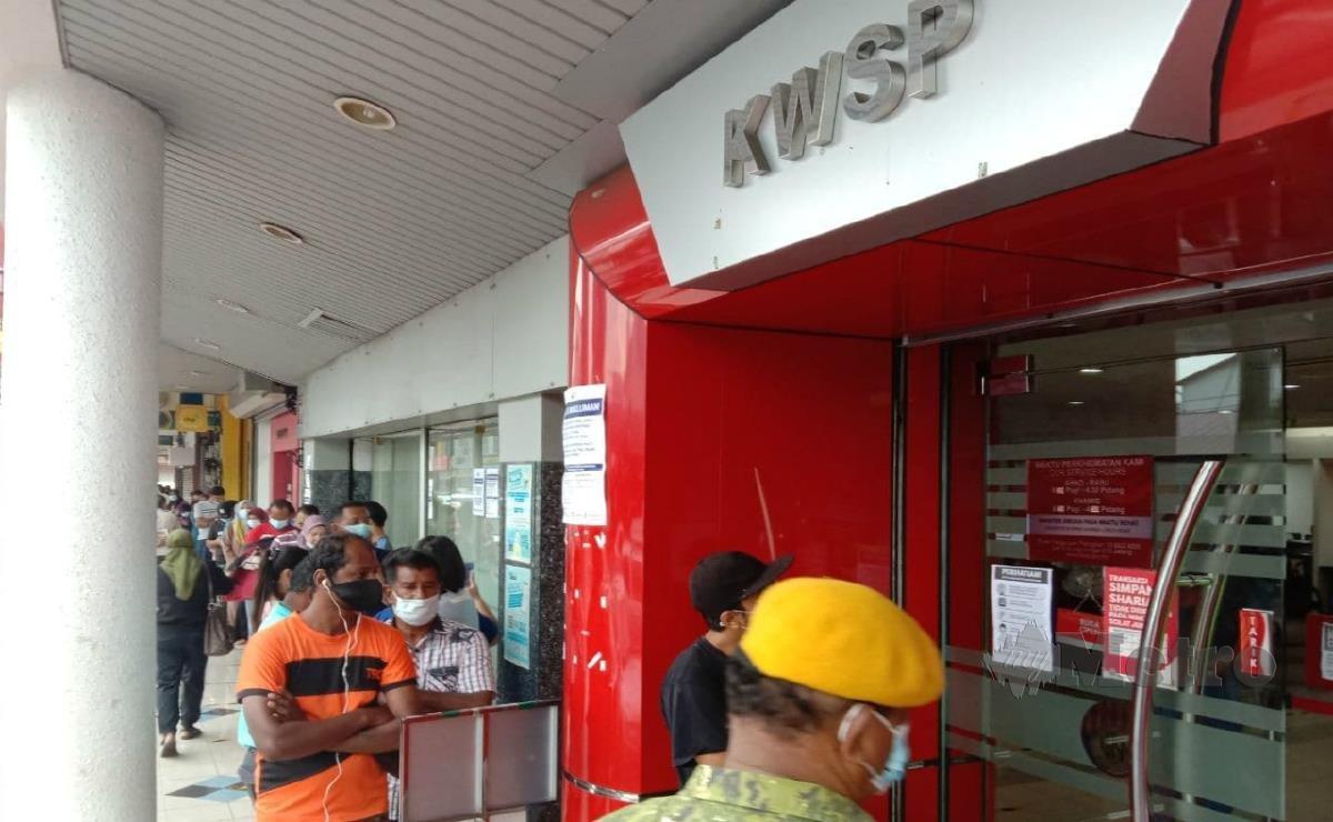ORANG ramai kelihatan beratur di sepanjang laluan premis untuk berurusan di pejabat KWSP Cawangan Kluang. FOTO Adnan Ibrahim.
